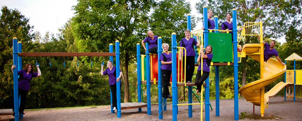 The Riverside Dental team posing on playground equipment